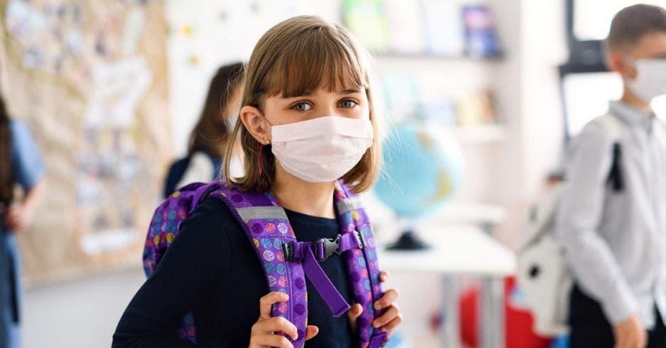 Una niña escolar con una mascarilla