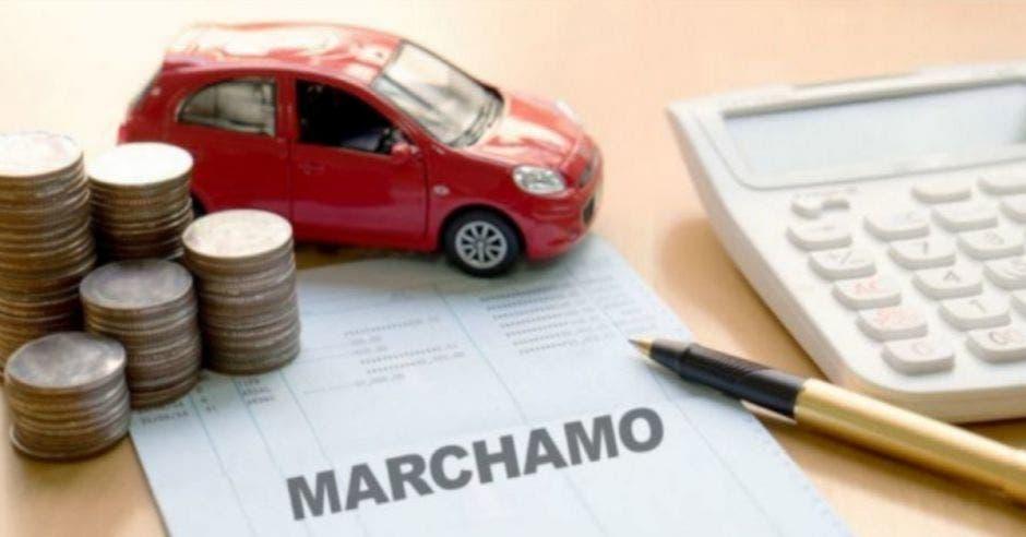 auto rojo pequeño junto a torres de monedas sobre hoja blanca al lado de un bolígrafo y calculadora