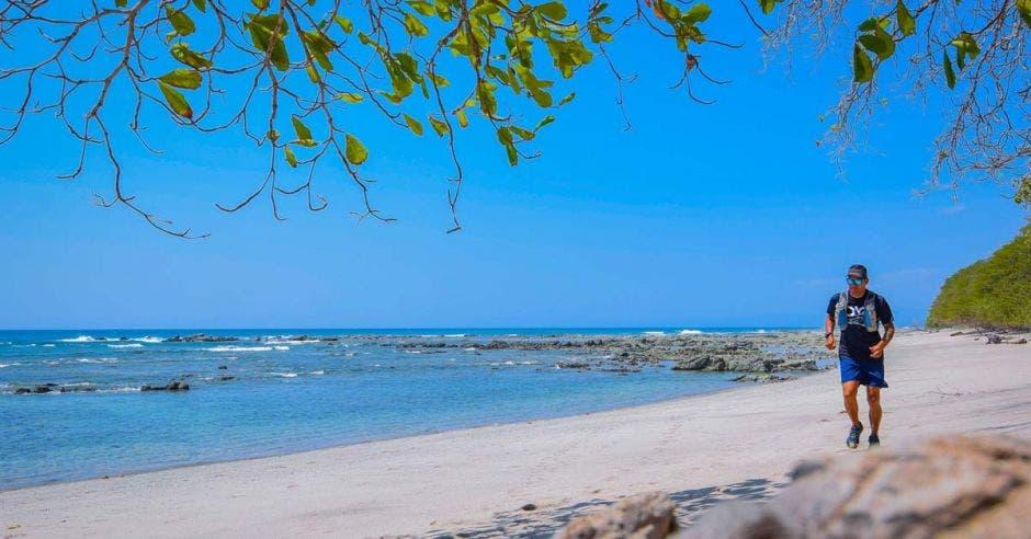 un hombre de estatura mediana corre por la arena en la playa