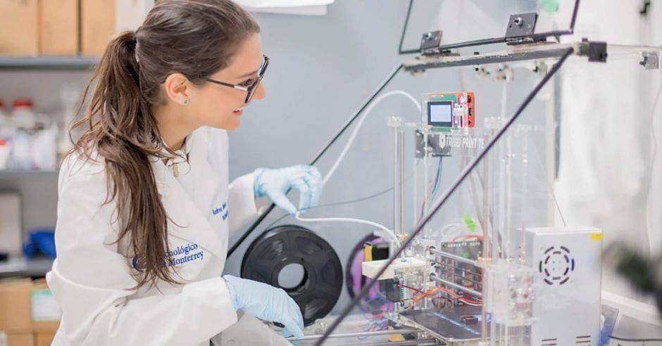 una mujer con una bata blanca y anteojos en un laboratorio
