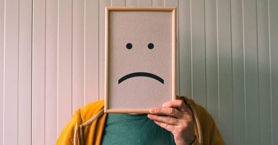Una persona sosteniendo con una mano un cuadro con una cara triste