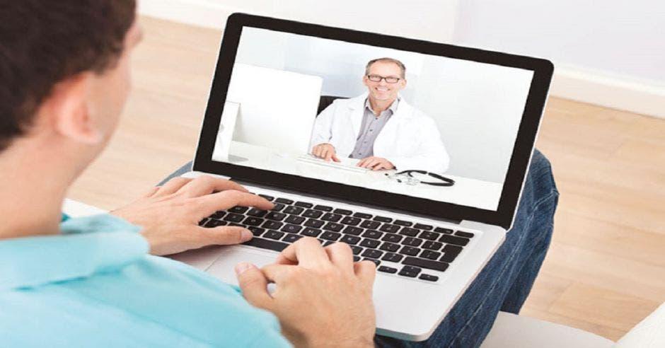 Una persona sosteniendo en sus manos una computadora y en la pantalla un doctor