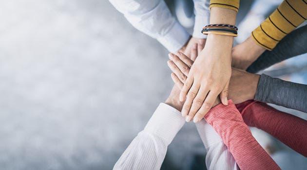 Cinco personas uniendo sus manos al centro