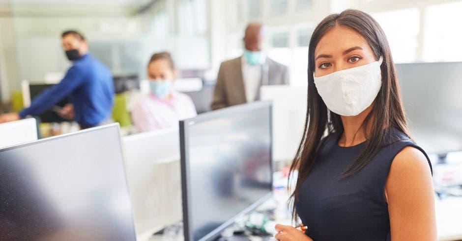 una mujer con mascarilla junto a una computadora