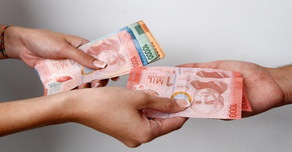 dos personas intercambiando billetes de distintas denominaciones