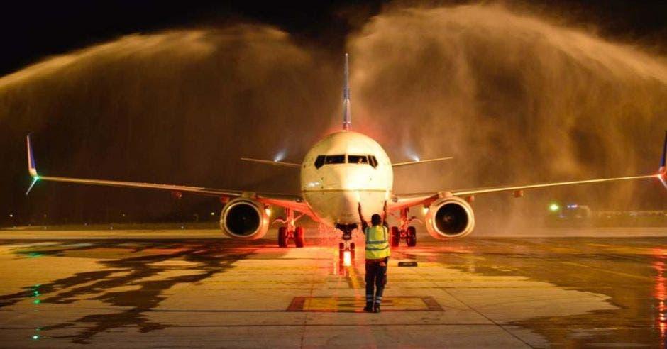 un avión aterrizando en un aeropuerto siendo roceado por agua