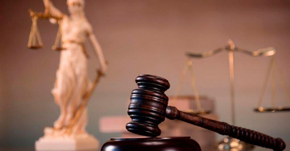 Imagen de un mazo junto a la dama de la justicia