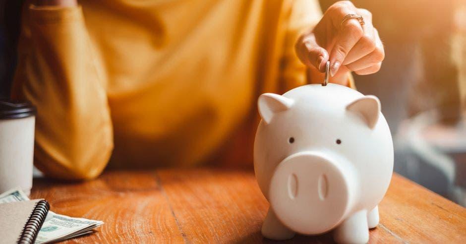 Persona depositando dinero en una alcancía