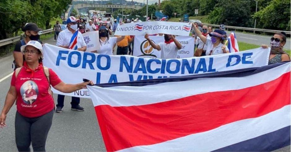 Personas protestando en calle con bandera de Costa Rica