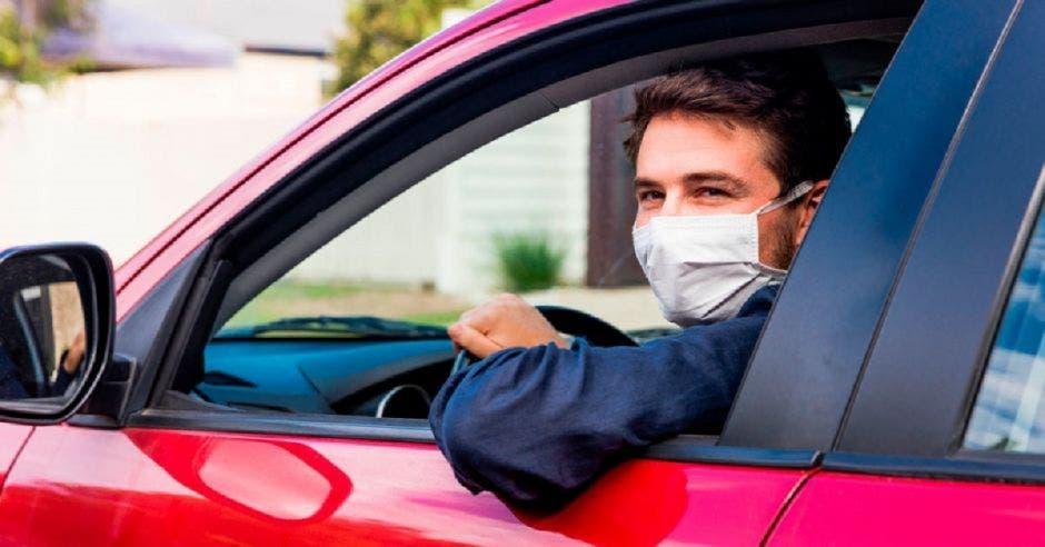 Una persona con mascarilla conduciendo un vehículo rojo