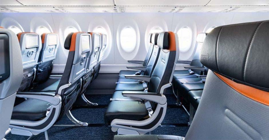 Interior de un avión. Asientos de cuero negro con detalles en naranja