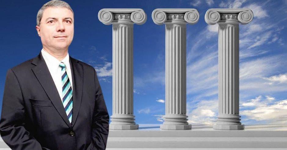 Hombre de traje y corbata frente a pilares de cemento