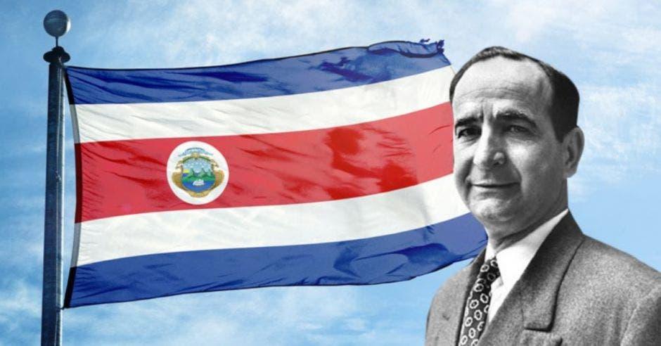"""Foto en blanco y negro de José """"Pepe"""" Figueres con bandera de Costa Rica de fondo"""