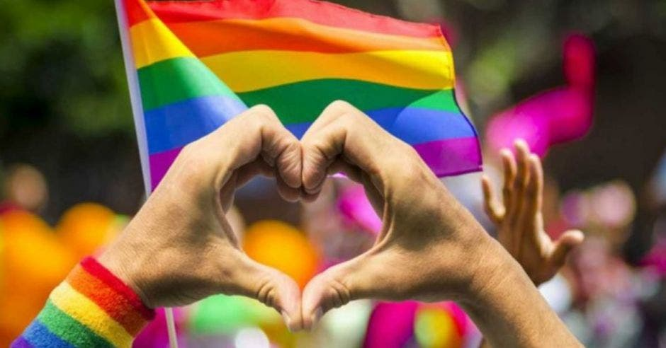 manos formando un corazón de fondo la bandera LGBT