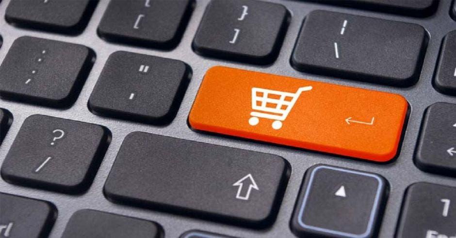 teclado de computadora con tecla naranja con dibujo de carrito de mercado