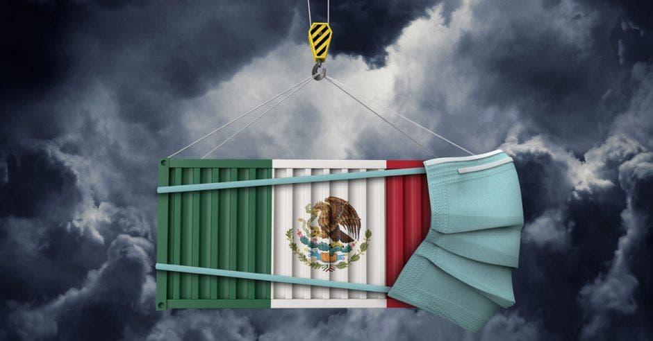 un contenedor con la bandera de México pintada y una mascarilla puesta. Fondo oscuro y nublado.