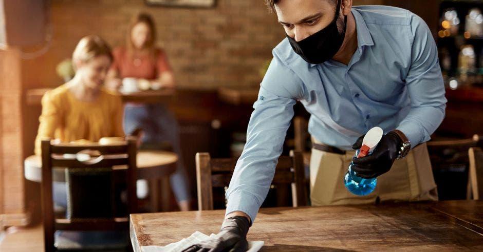 un mesero con mascarilla limpiando una mesa