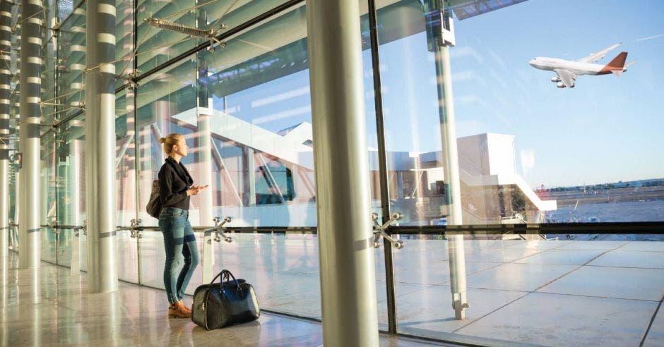 una mujer divisa un avión a través del cristal del lobby del aeropuerto