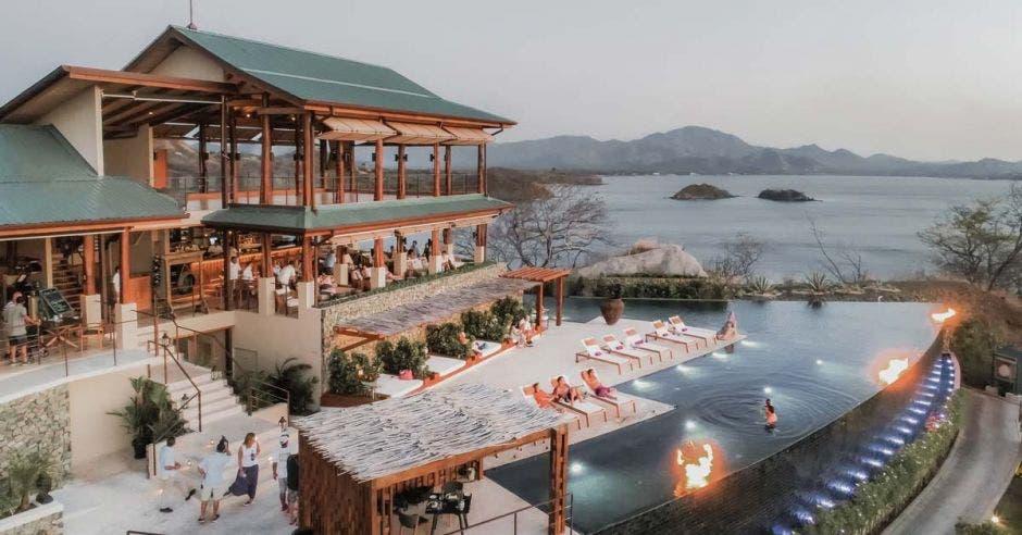 imagen de un hotel de playa de noche. Tiene piscina infinita.
