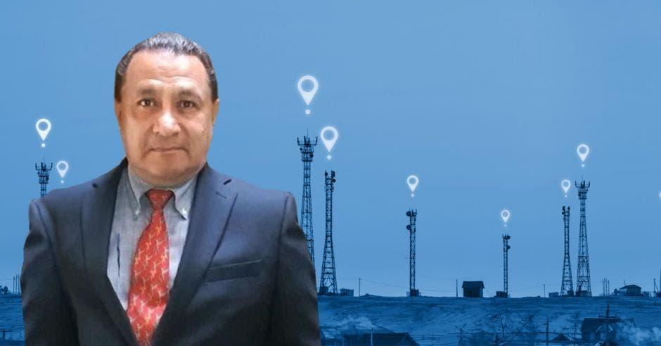 señor con traje azul y corbata roja, de fondo antenas de telecomunicaciones