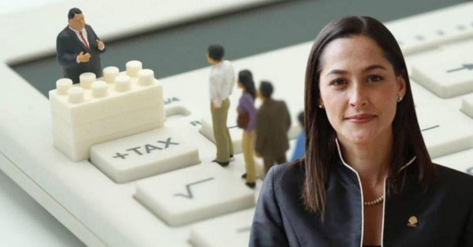 . mujer de cabello castaño con saco negro, de fondo un teclado blanco con figuras de personas formadas