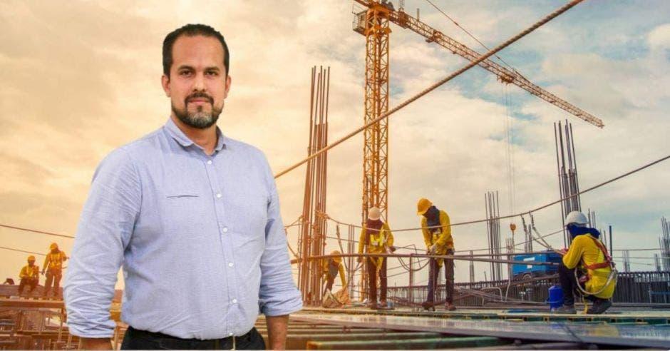 hombre con barba con camisa azul, fondo de una construcción con obreros