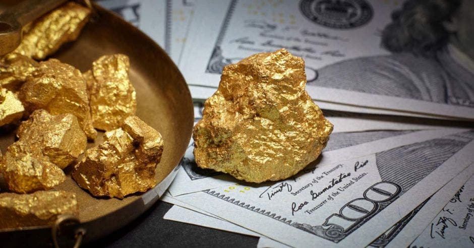 una pepita de oro sobre un fajo de billetes de 100 dólares