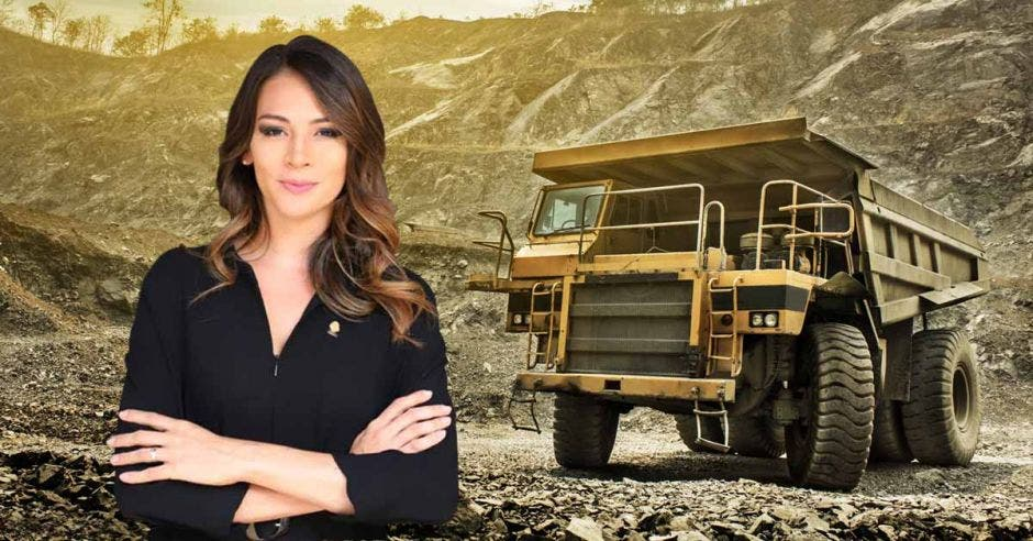 una mujer de vestido negro sobre un fondo que presenta un camión que carga piedras