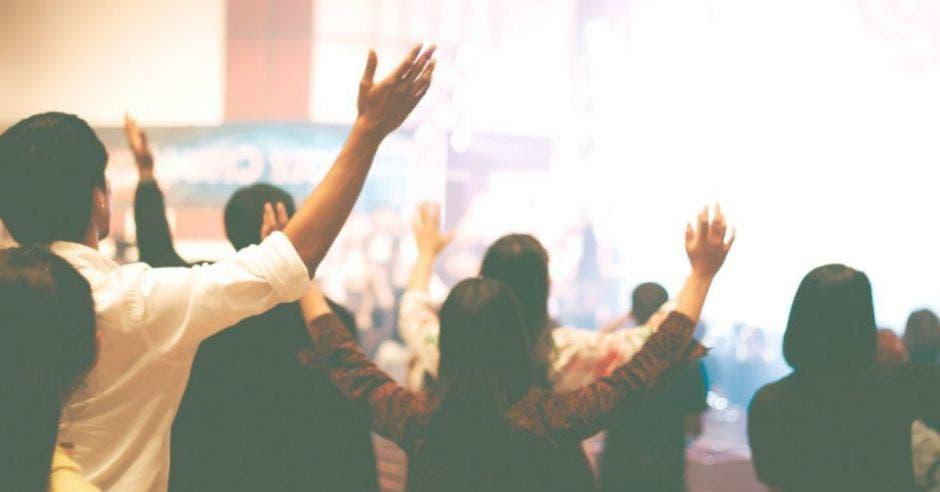personas de espaldas levantando las manos