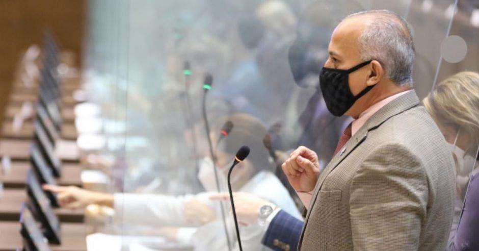 señor de traje gris claro con cubrebocas negro frente a un micrófono