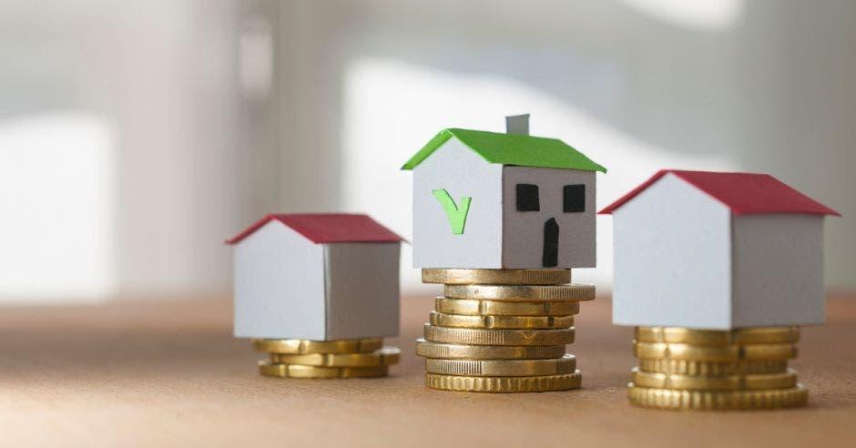 casas pequeñas sobre torres de monedas de diferentes tamaños