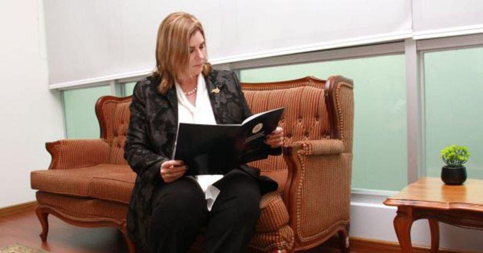Una mujer de traje negro y blusa blanca sostiene un libro