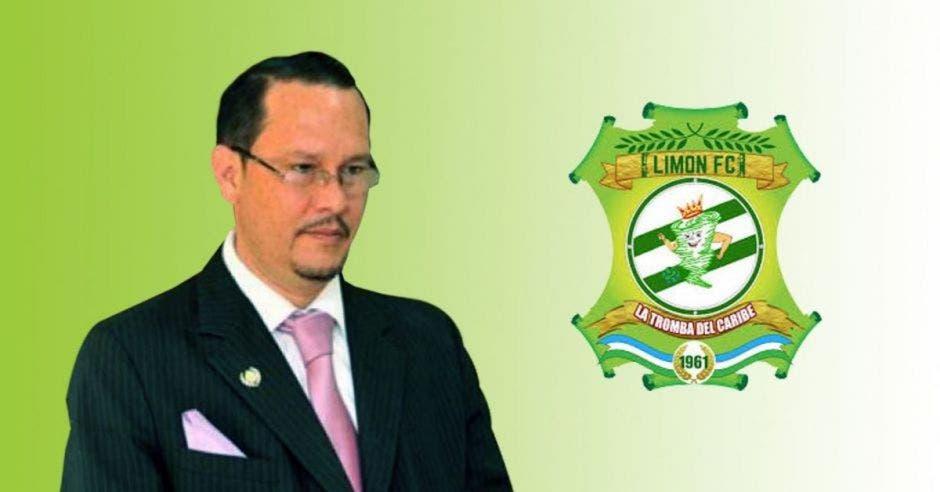 hombre de lentes con traje negro de rayas y corbata rosa, detrás el logotipo del equipo de futbol Limón