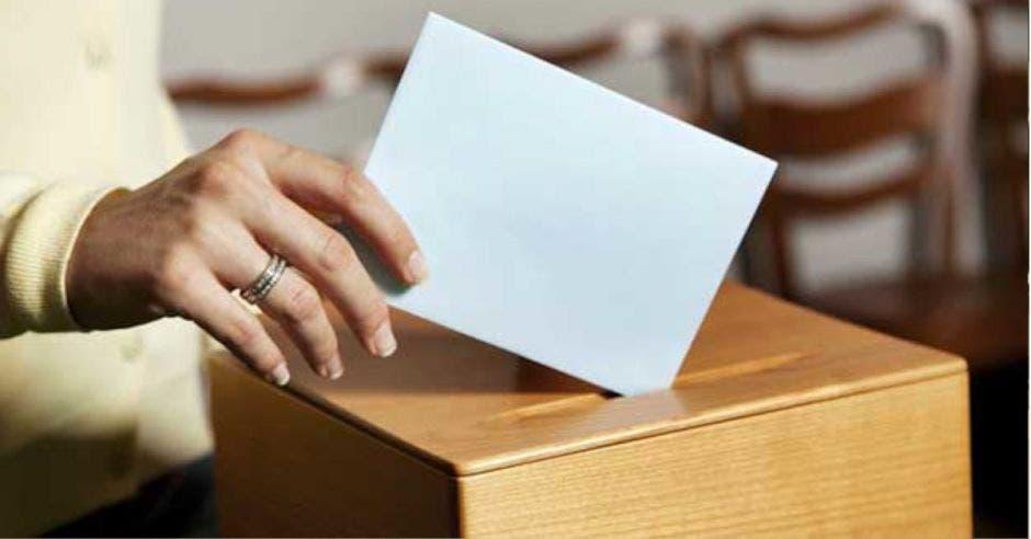 mano depositando papeleta blanca en una casilla