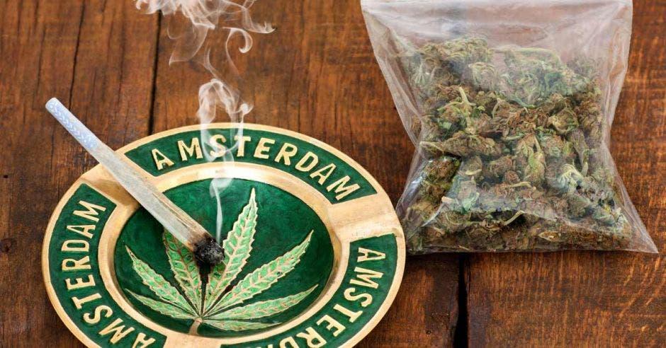 Puro de marihuana en un cenicero con cartel de Amsterdam y una gran bolsa de plástico de marihuana sobre fondo de madera