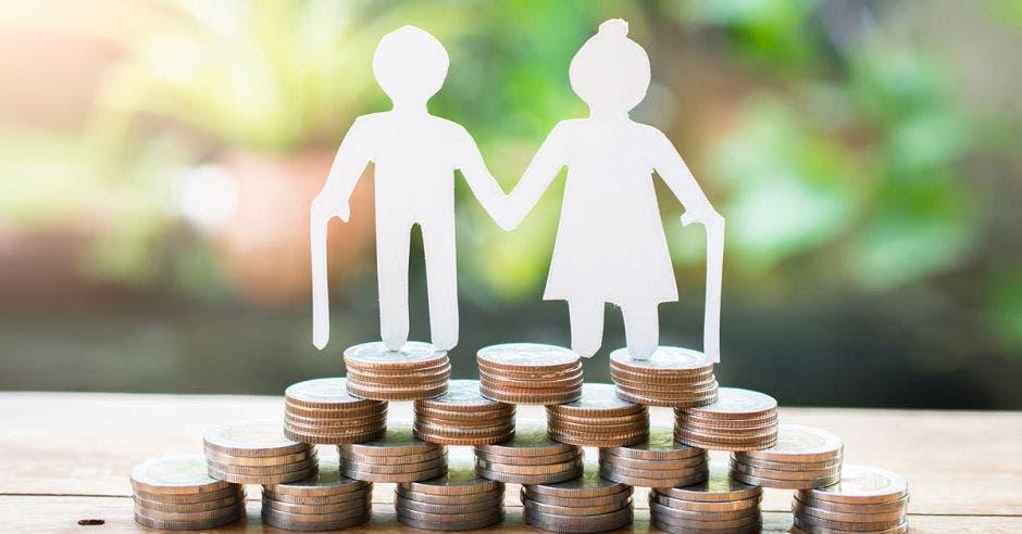 figuras de personas mayores sobre torres de monedas