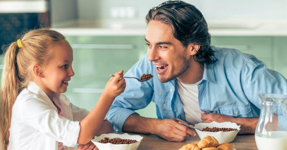 Niña y papá comiendo cereal