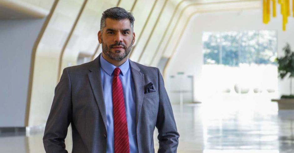 un hombre de saco gris, camisa celeste y corbata roja