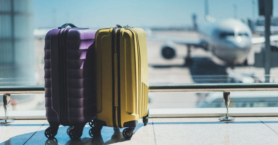 Maletas en la sala de salida del aeropuerto, avión en segundo plano, concepto de vacaciones de verano