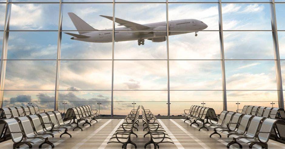 Una sala de espera de una aeropuerto y detrás de las ventanas un avión en ascenso