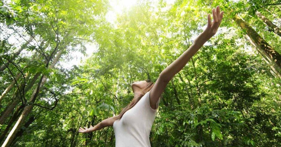 una mujer toma aire sobre un fondo verde