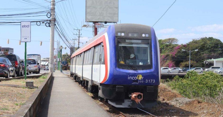 un tren tricolor con azul, blanco y rojo, recorre la ciudad a través de la línea férrea