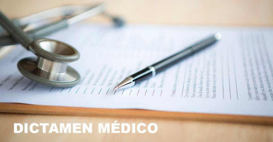 Una tabla con una hoja y encima un estetoscopio y un lapicero con la palabra dictamen médico