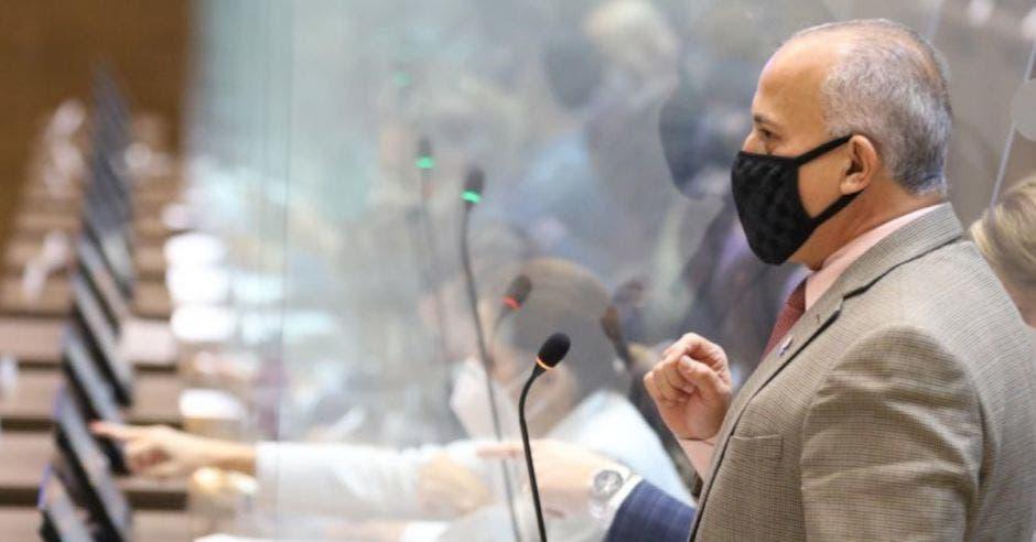 hombre de traje café claro con mascarilla negra frente a un micrófono
