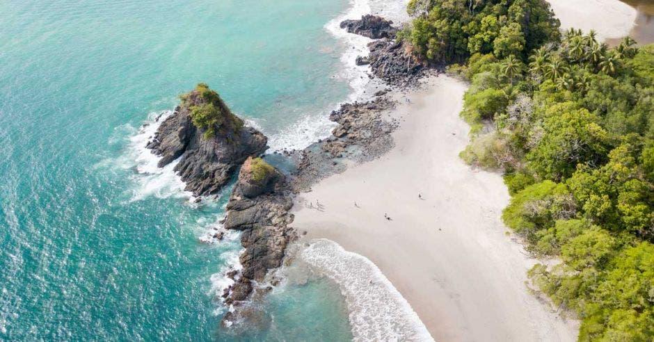 un islote rodeado de agua marina y playa