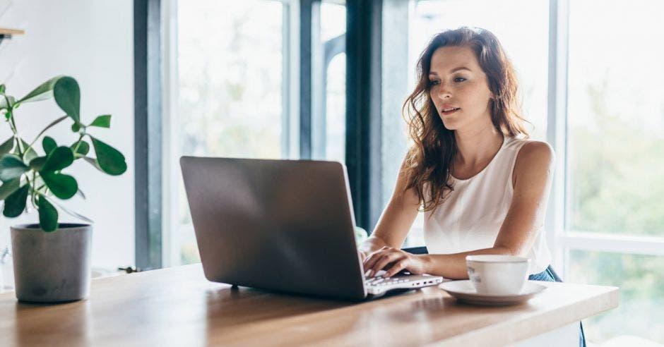 Mujer usando un portátil mientras se sienta en casa