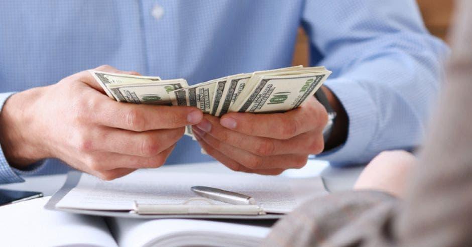 Hombre cuenta dólares