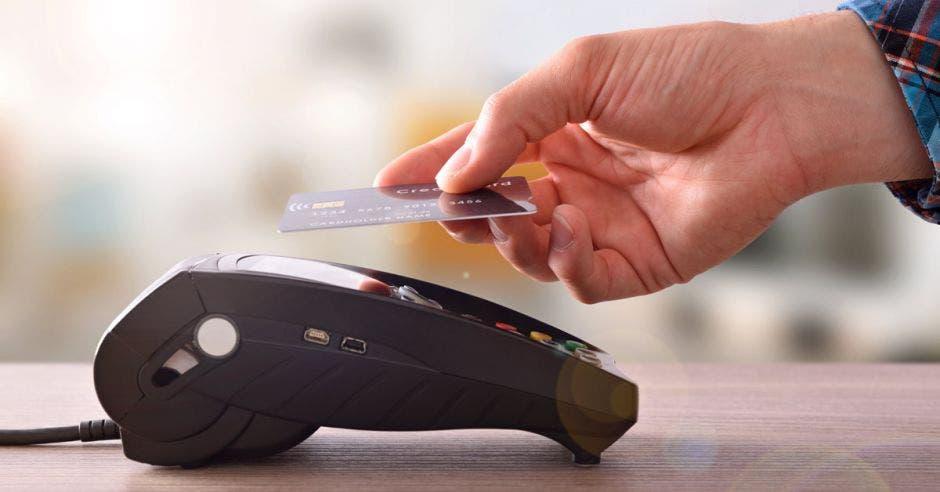 mano sosteniendo tarjeta bancaria cerca de terminal para hacer pago sin contacto