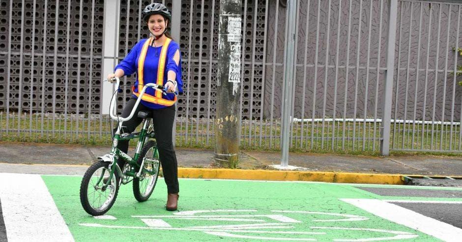 una mujer en bicicleta sobre una demarcación verde