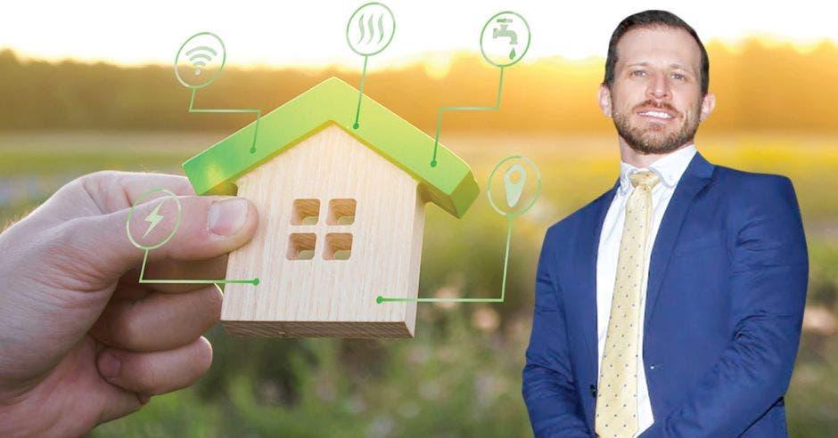 hombre de traje azul y cabello castaño, junto a figura de madera de una casa con techo verde